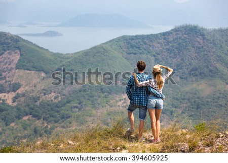 Couple traveling: admiring great view of hills, lagoon and small islands, while hiking in asia together