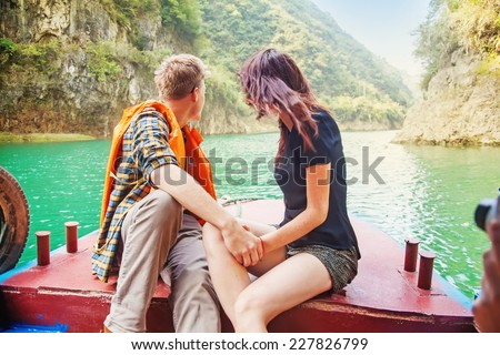 couple traveling by boat (back view) - stock photo
