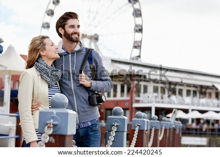 couple traveling together having fun near ferris wheel attraction