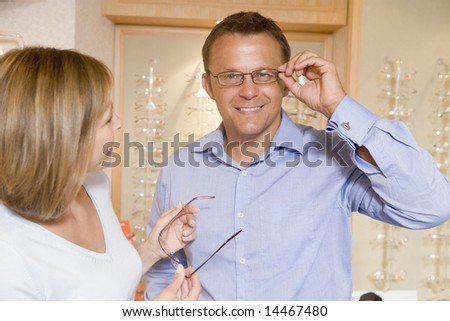 Couple trying on eyeglasses at optometrists smiling