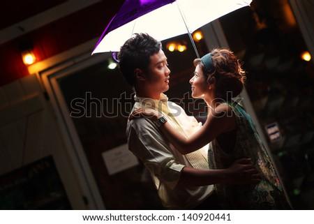 Couple under umbrella at night - stock photo