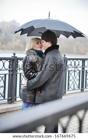 Couple under umbrella on the bridge - stock photo