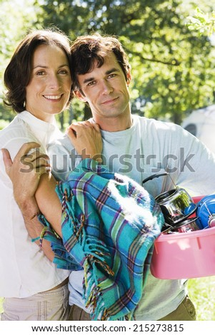 Couple unloading car on camping trip, man carrying picnic blanket and pink container, smiling, portrait