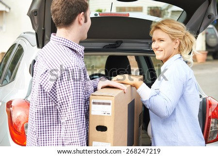 Couple Unloading New Television From Car Trunk - stock photo