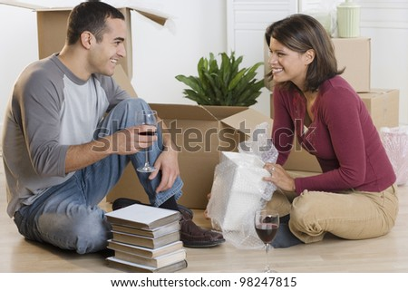 Couple unpacking boxes and drinking wine