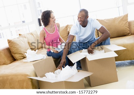 Couple unpacking boxes in new home smiling - stock photo