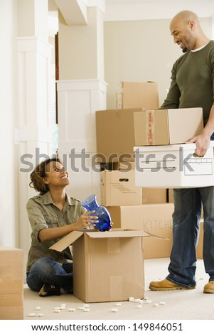 Couple unpacking in new house - stock photo