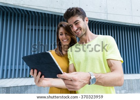 Couple use of the tablet at outdoor - stock photo