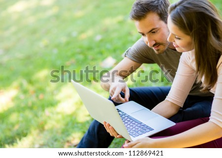 Couple using a laptop outdoors and looking happy - stock photo