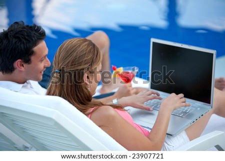 couple using a laptop while relaxing by the swimming pool - stock photo