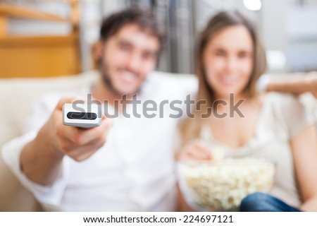Couple using a remote control while sitting on the couch - stock photo