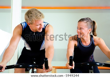 Couple using bikes in a club, looking at each other - stock photo