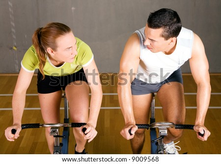 Couple using bikes in a fitness club, looking at each other competitively