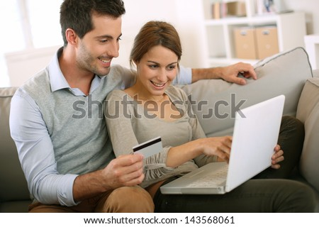 Couple using credit card to shop on internet - stock photo