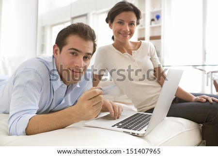 Couple using credit card to shop on line. Laptop.indoor on couch - stock photo