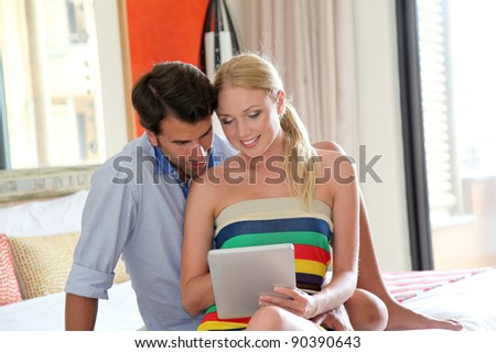 Couple using electronic tablet in hotel room - stock photo