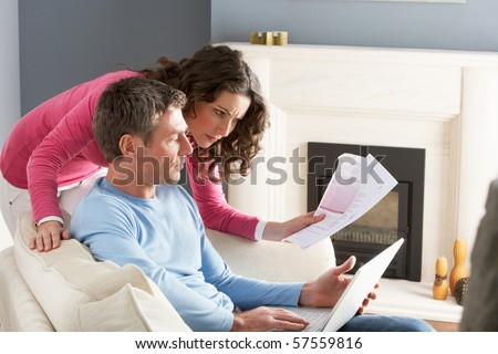 Couple Using Laptop And Discussing Household Bills Sitting On Sofa At Home - stock photo