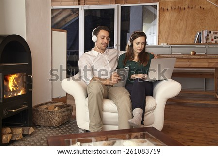 Couple using laptop and tablet listening to music
