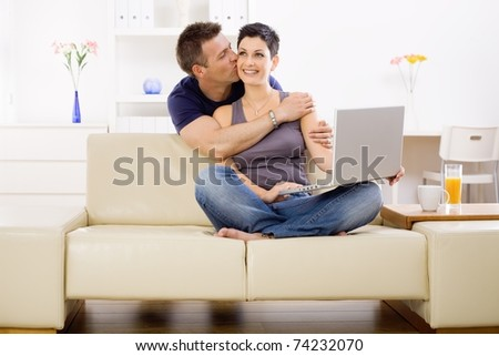 Couple using laptop computer at home together, man hugging and kissing woman, smiling.? - stock photo