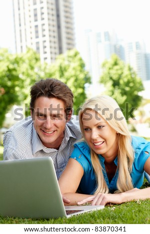 Couple using laptop in city park - stock photo