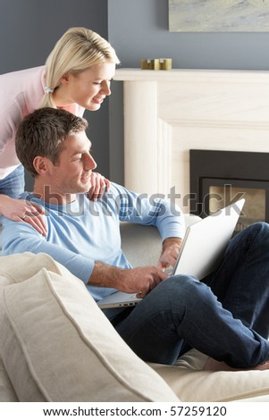 Couple Using Laptop Relaxing Sitting On Sofa At Home - stock photo