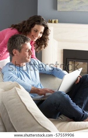 Couple Using Laptop Relaxing Sitting On Sofa At Home