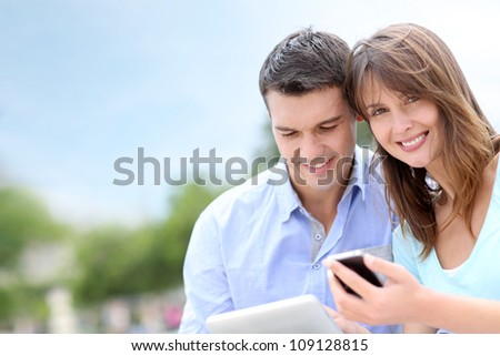 Couple using tablet and cellphone in public park - stock photo