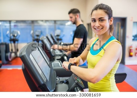 Couple using treadmills together at the gym - stock photo