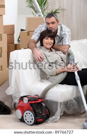 Couple vacuuming house before moving - stock photo