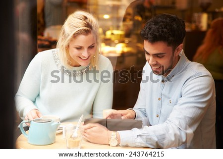 Couple Viewed Through Window Of Caf�¢?? Using Digital Tablet - stock photo