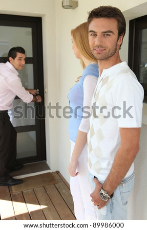 Couple visiting a property with an estate agent - stock photo