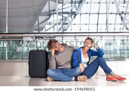 couple waiting at airport terminal - stock photo
