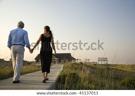 Couple walk hand in hand on a boardwalk towards a beach pavilion. Horizontal shot.