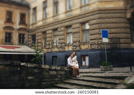 couple walk in old town lvov,huseband sit with his wife