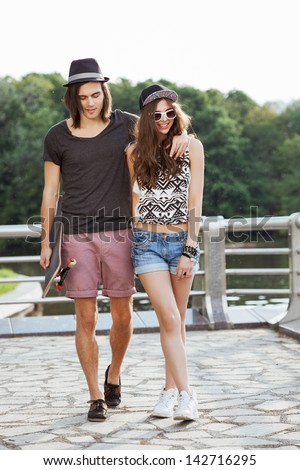 Couple walk on the bank of a river. Young active people. Outdoors, lifestyle - stock photo