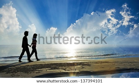 couple walk together on the beach in morning - stock photo