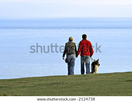 Couple walking a dog - hand in hand by the sea - stock photo