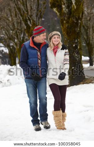 Couple Walking Along Snowy Street In Ski Resort - stock photo
