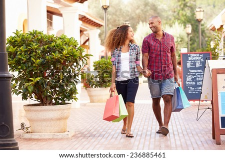 Couple Walking Along Street With Shopping Bags - stock photo