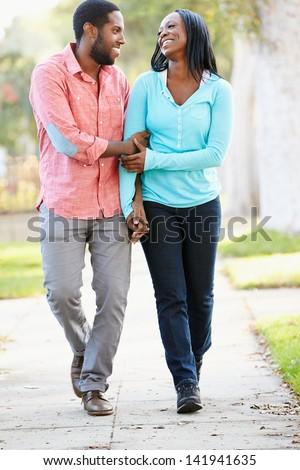 Couple Walking Along Suburban Street Together - stock photo