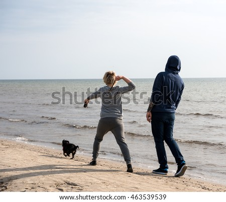 Couple walking along the beach with a dog.