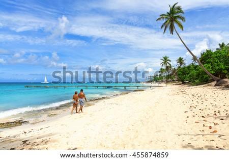 Couple walking along the tropical coast of the Dominican Republic. Tropical beach. - stock photo