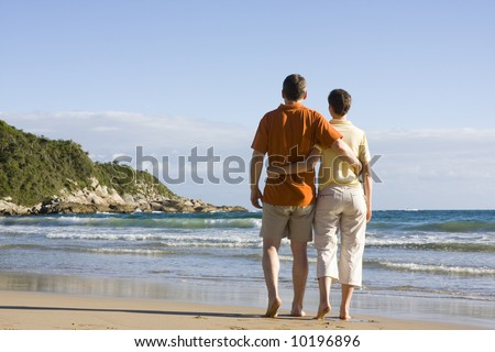 Couple walking arm in arm on a tropical beach - stock photo