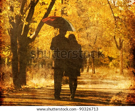 Couple walking at alley in autumn park. Photo in old image style. - stock photo