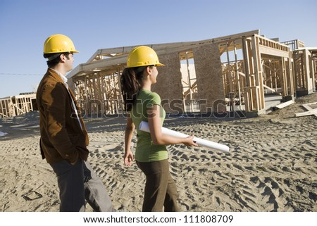 Couple walking at construction site - stock photo