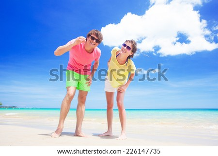 couple walking at tropical beach - stock photo