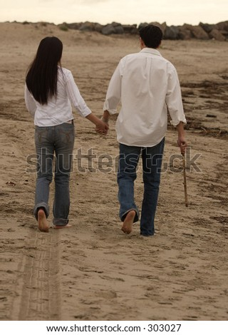 COUPLE WALKING AWAY to the sunset - stock photo
