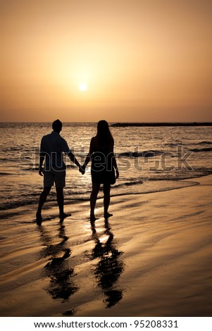 Couple walking by sea shore in the evening looking at beautiful sunset