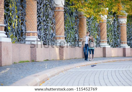Couple walking by the beautiful grill of Mikhailovsky (Michael) garden of Saint-Petersburg - stock photo
