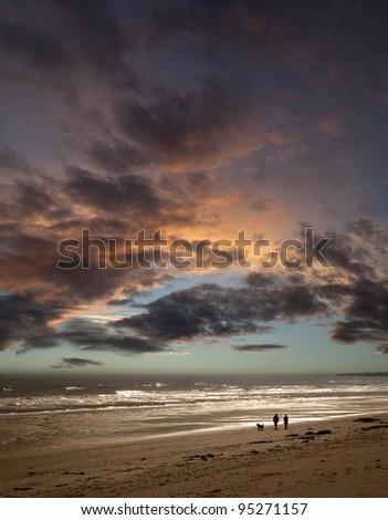 Couple walking dog on beach at sunset - stock photo